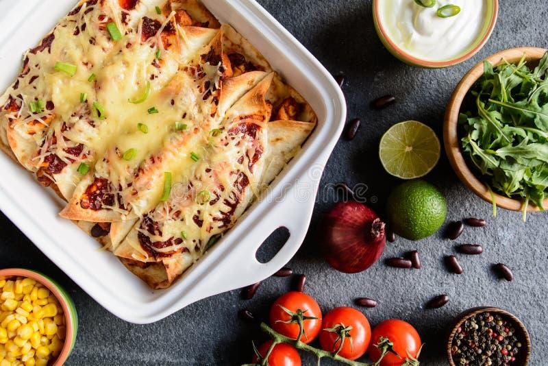 Enchiladas del pollo con salsa al pomodoro, mais, i fagioli ed il formaggio piccanti immagini stock libere da diritti