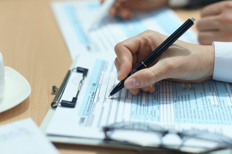 Enchimento da mulher em U S Declaração de rendimentos individual da renda, imposto 1040 na tabela foto de stock royalty free