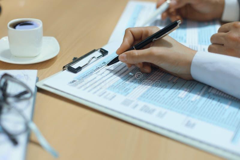 Enchimento da mulher em U S Declaração de rendimentos individual da renda, imposto 1040 na tabela fotos de stock royalty free