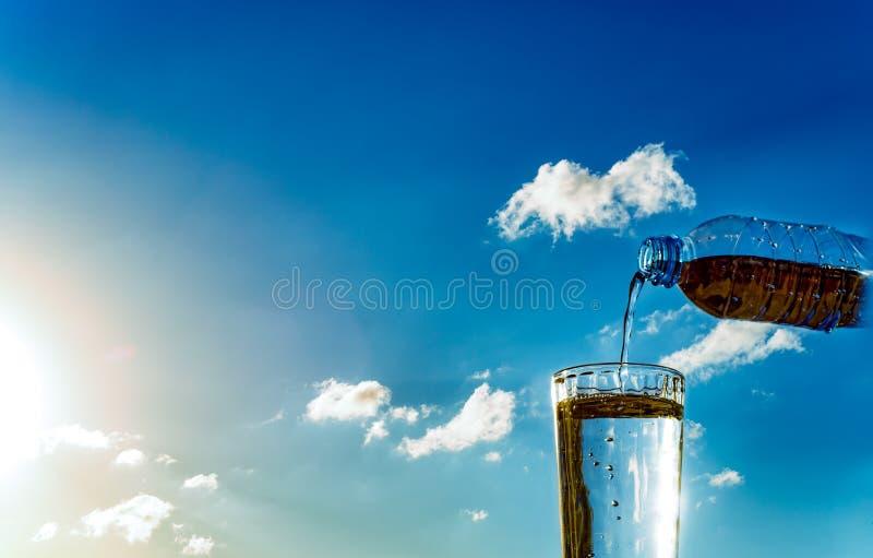 Enchimento de um vidro pela água contra o céu imagens de stock