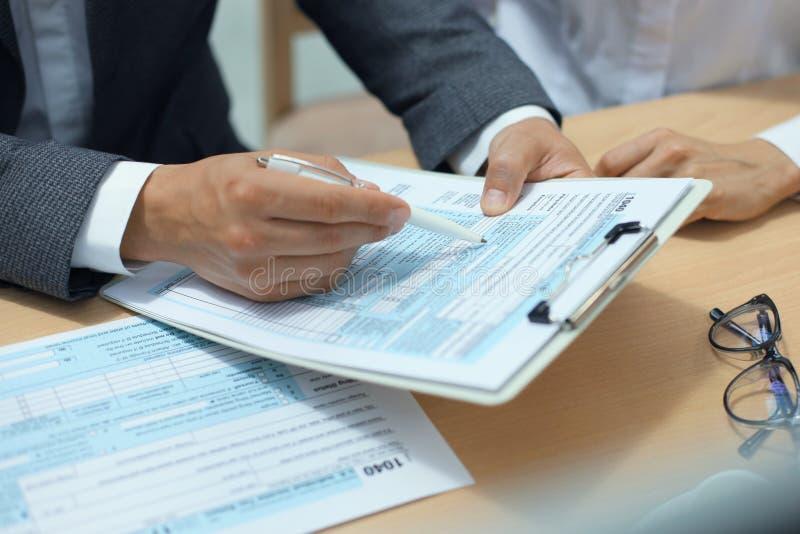 Enchimento do homem em U S Declaração de rendimentos individual da renda, imposto 1040 na tabela imagens de stock