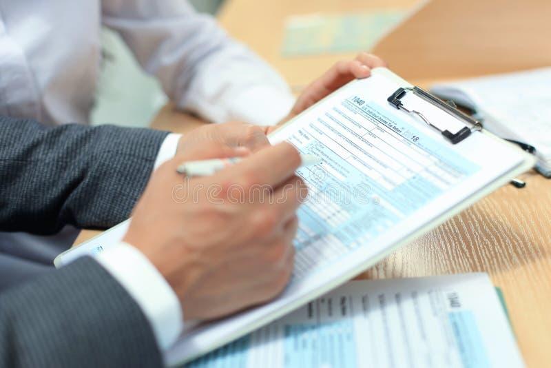 Enchimento do homem em U S Declaração de rendimentos individual da renda, imposto 1040 na tabela fotografia de stock royalty free
