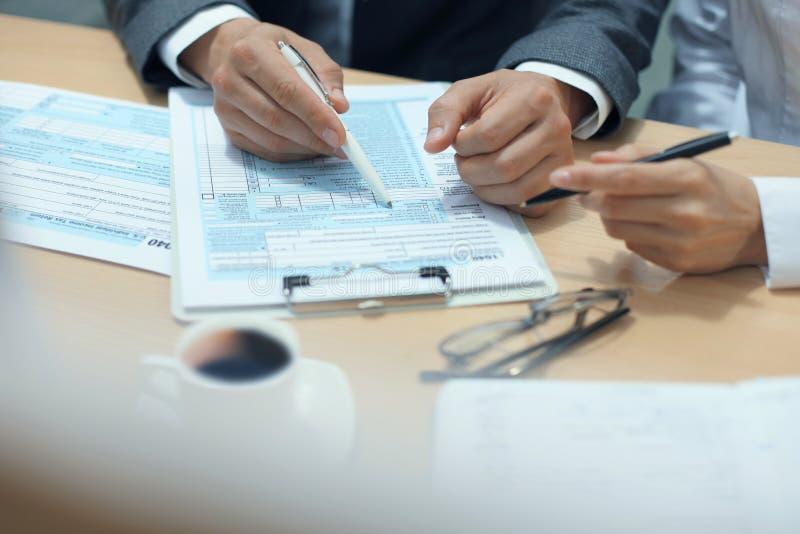 Enchimento do homem em U S Declaração de rendimentos individual da renda, imposto 1040 na tabela fotos de stock