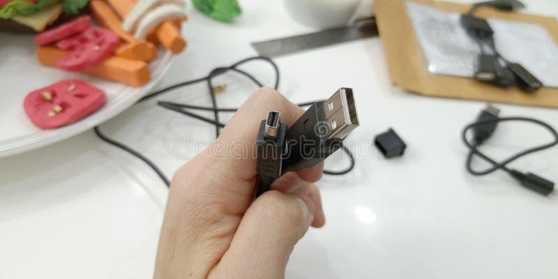 Enchufe de HDMI y del USB para la cámara al ordenador, herramientas del trabajo del equipo en mi mano a mostrar para tomar una fo fotografía de archivo