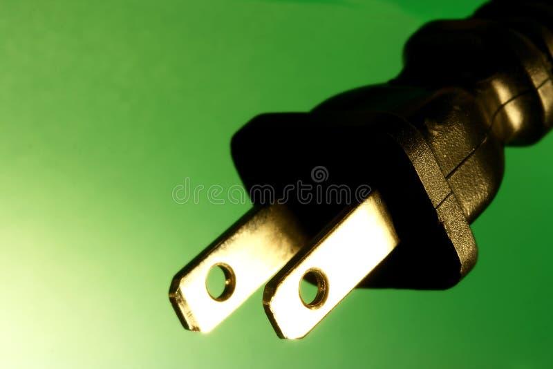 Enchufe eléctrico contra fondo verde fotos de archivo