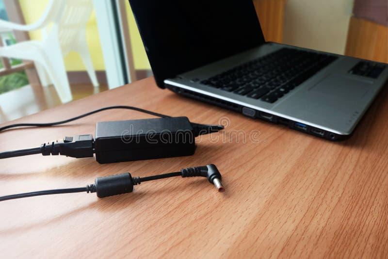 Enchufe el cargador del cable eléctrico del adaptador del ordenador portátil en de madera fotos de archivo libres de regalías