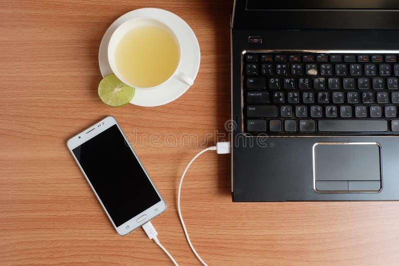 Enchufe el cargador del cable USB del teléfono móvil con un ordenador portátil y recientemente un zumo de lima en una taza blanca imágenes de archivo libres de regalías