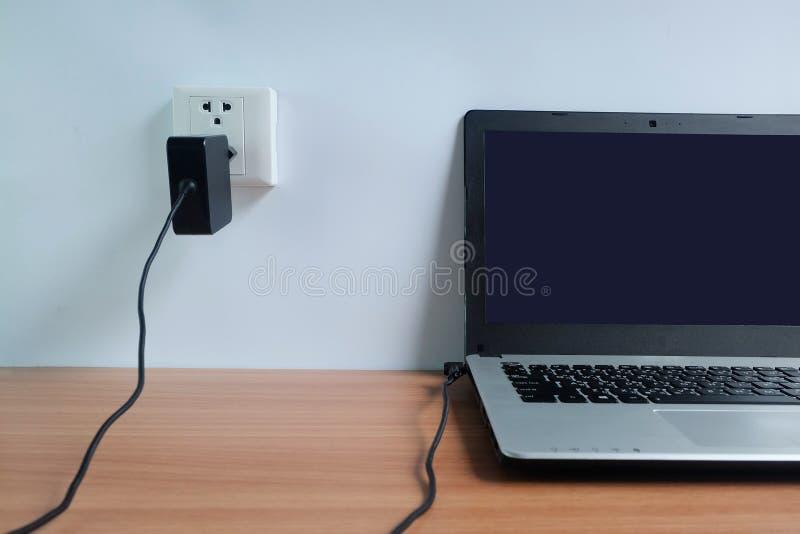 Enchufe el cargador del cordón del adaptador de la toma de corriente en una pared blanca del ordenador portátil en de madera foto de archivo libre de regalías