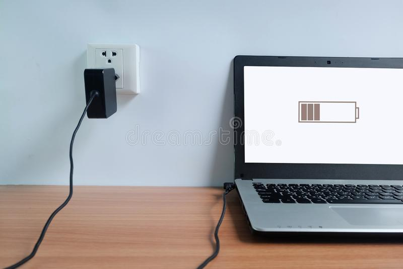 Enchufe el cargador del cordón del adaptador de la toma de corriente en una pared blanca del ordenador portátil en de madera fotografía de archivo libre de regalías