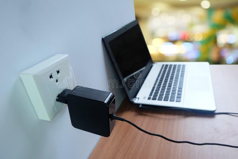 Enchufe el cargador del cordón del adaptador de la toma de corriente en una pared blanca del ordenador portátil en de madera fotos de archivo