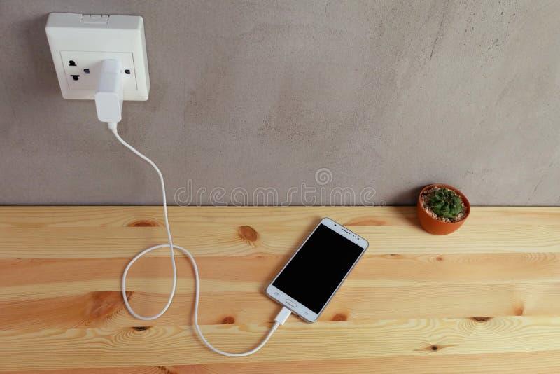 Enchufe el cargador del cordón del adaptador de la toma de corriente del teléfono móvil en de madera imágenes de archivo libres de regalías