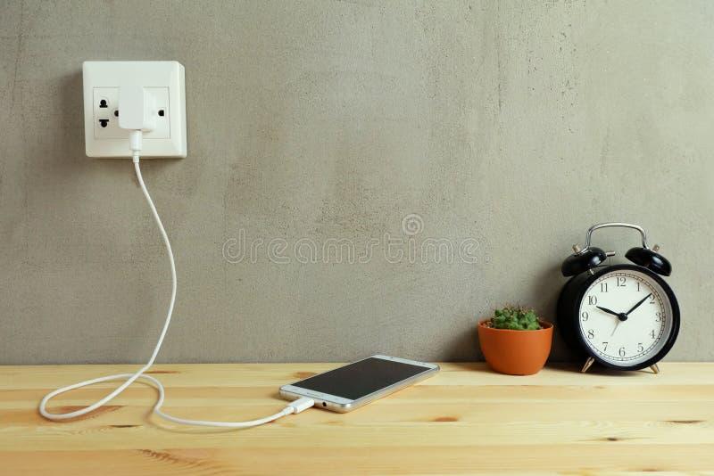 Enchufe el cargador del cordón del adaptador de la toma de corriente del teléfono móvil en de madera foto de archivo