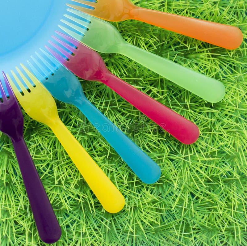 Enchufes coloreados en el césped verde, comida campestre, diversión, huéspedes, visión superior fotos de archivo libres de regalías
