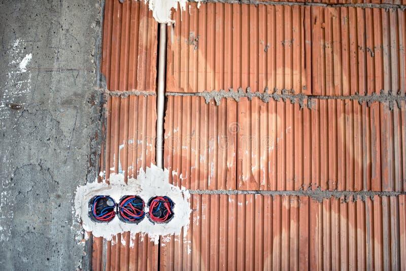 Enchufes de pared, instalación de la electricidad en el emplazamiento de la obra de la casa foto de archivo libre de regalías