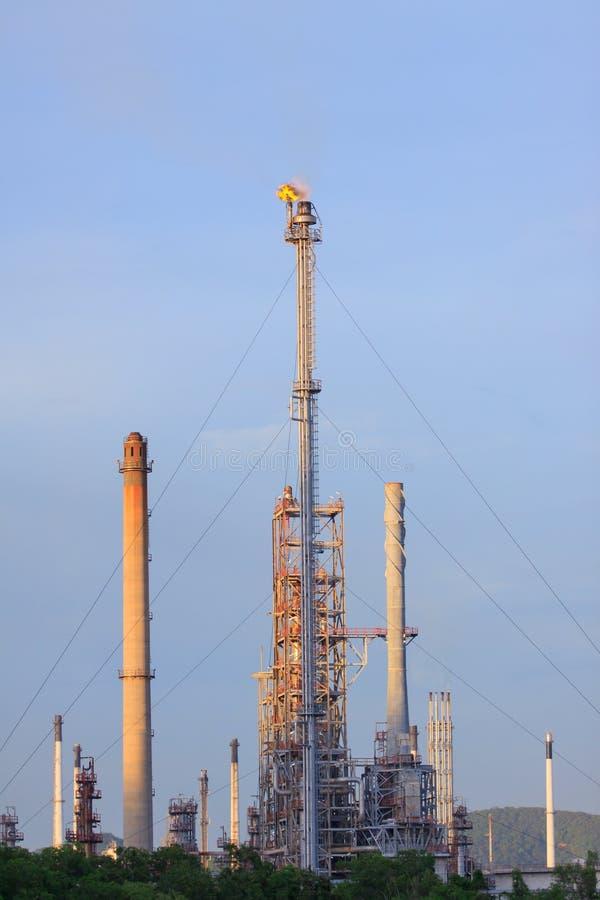 Encienda el burning sobre la chimenea de la refinería de petróleo contra el cielo azul imagenes de archivo