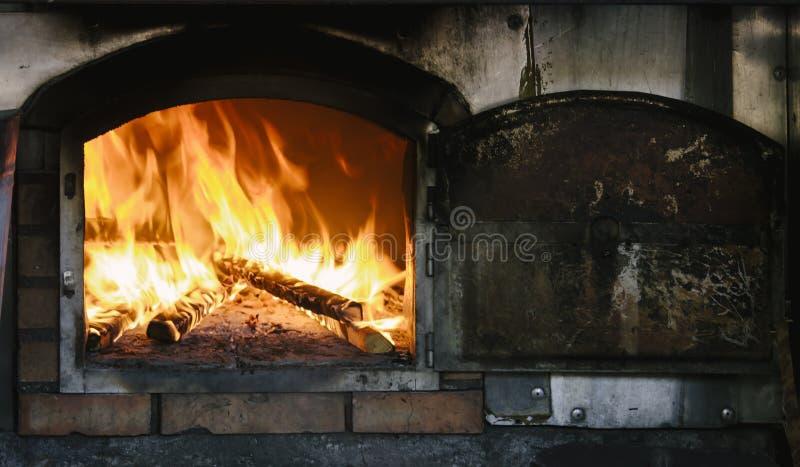 Encienda el rugido y la quema de madera en el horno tradicional de la albañilería, también conocido como el horno del ladrillo u  imagenes de archivo