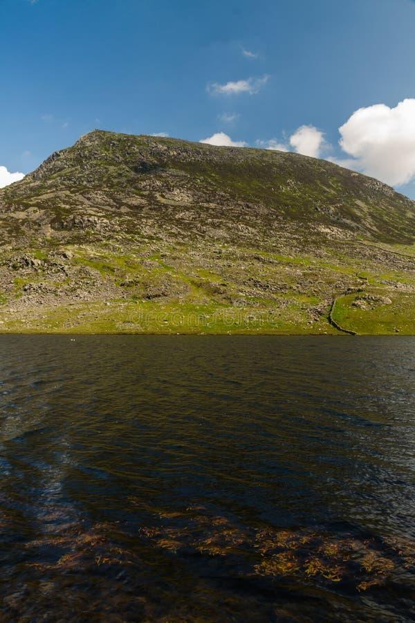 Encierre la montaña del año Ole Wen con el lago Llyn Ogwen en el primero plano foto de archivo