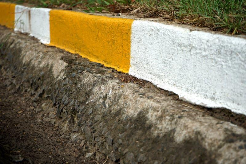 Encintado concreto y canal blancos y amarillos imagen de archivo libre de regalías