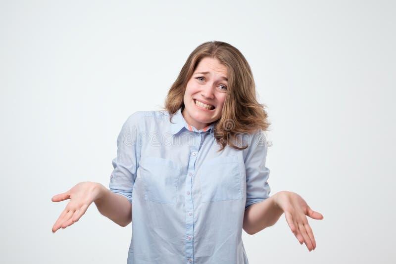 Encogimiento de la mujer europea que lleva la camisa azul en la duda que hace encogimiento de hombros fotos de archivo libres de regalías
