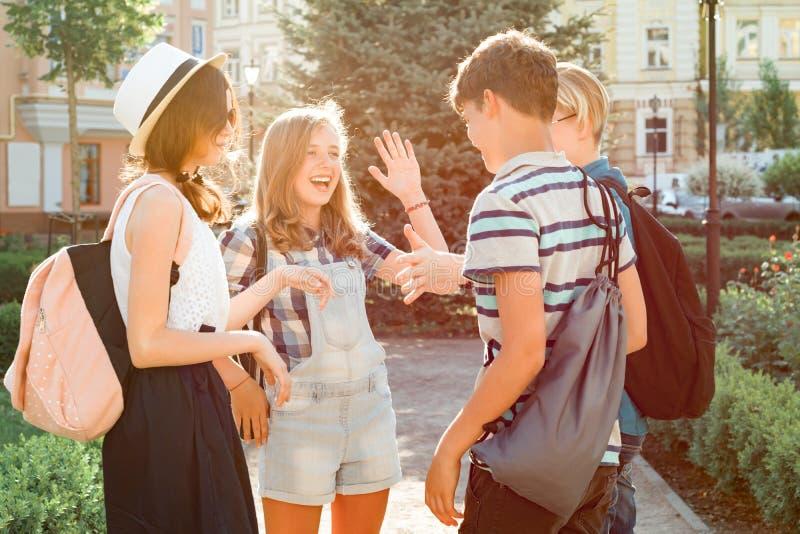 Encontrando adolescentes de sorriso dos amigos na cidade, jovens felizes que cumprimentam-se, abraçando dando altamente cinco Ami imagem de stock