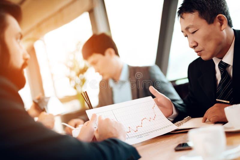 Encontrando homens de negócios chineses no restaurante Estão discutindo o gráfico de negócio imagens de stock royalty free