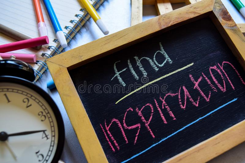 Encontre a inspiração em escrito à mão colorido da frase no quadro, no despertador com motivação e nos conceitos da educação imagem de stock