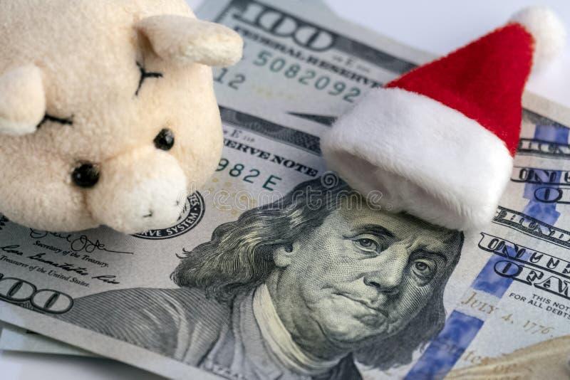 Encontre o ano novo sem débitos financeiros As mentiras do chapéu da Santa na cabeça de Franklin em cem dólares, em um porco maci fotos de stock