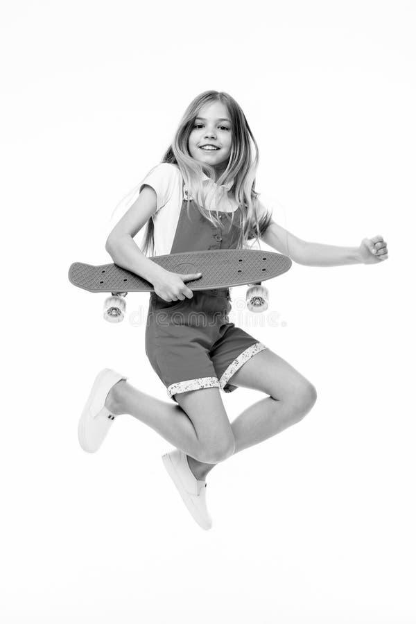 Encontre sua liberdade A menina pequena salta com a placa do patim isolada no branco Sorriso do skater da criança com longboard C imagem de stock