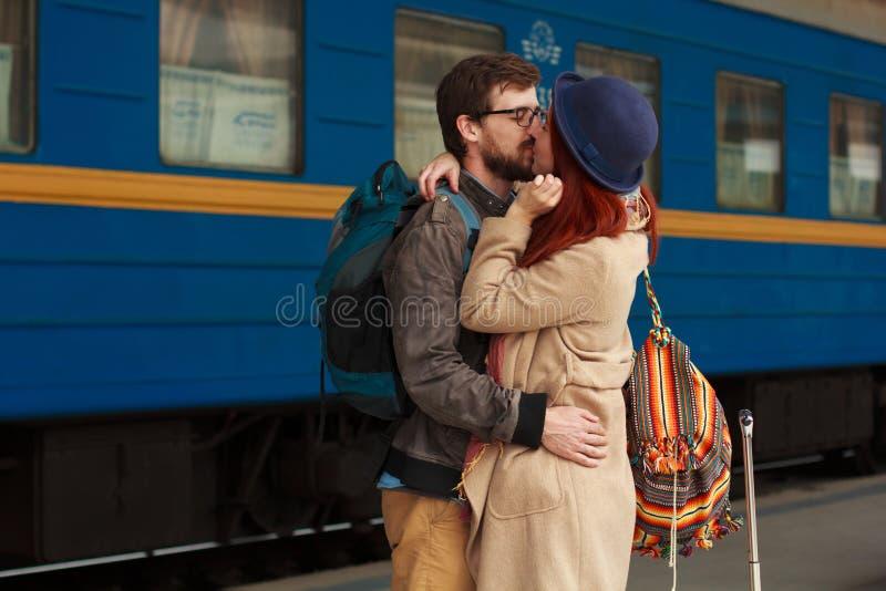 Encontro após um curso de um par feliz que abraça na rua em um estação de caminhos-de-ferro Luz solar morna da noite bonita foto de stock