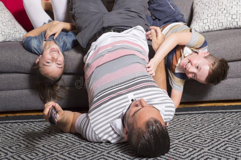 Encontro da família de cabeça para baixo no sofá imagens de stock