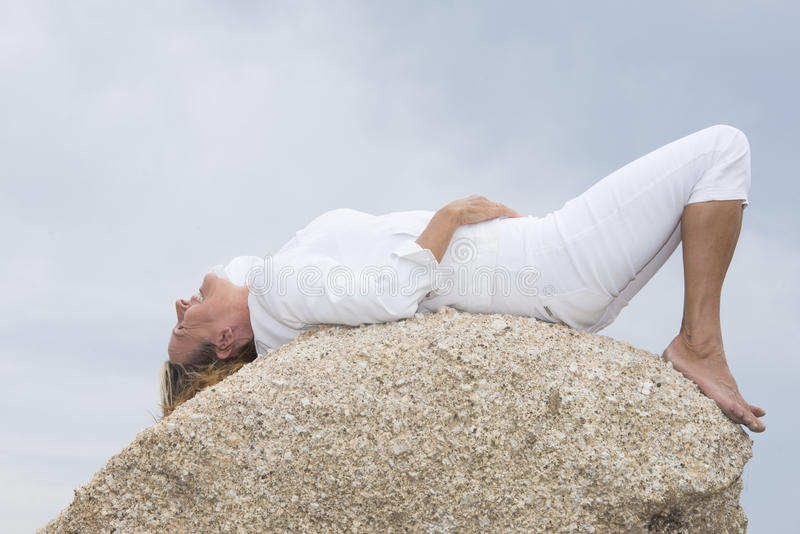 Encontro da mulher relaxado sobre a rocha exterior fotografia de stock royalty free