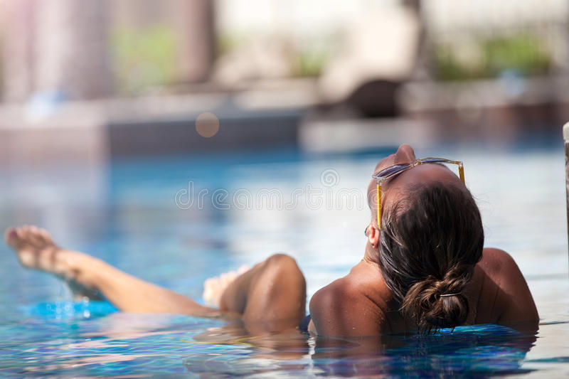 Encontro de relaxamento da mulher 'sexy' para baixo na piscina luxuosa imagens de stock