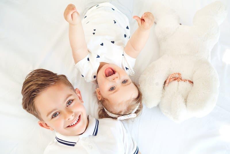 Encontro de sorriso das crianças positivas em uma cama branca imagem de stock