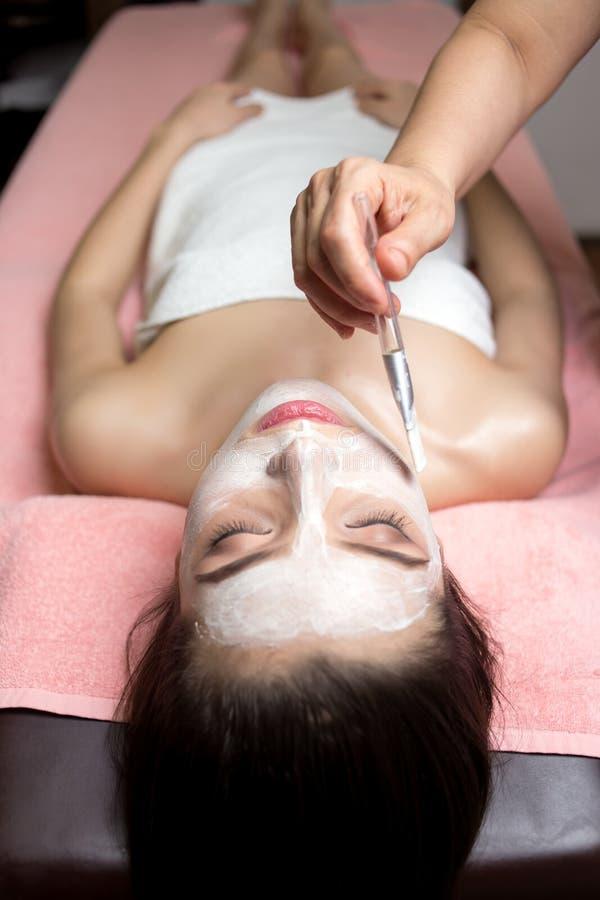 Encontro e cosmetologist da mulher que aplicam a máscara facial pela escova nos termas foto de stock