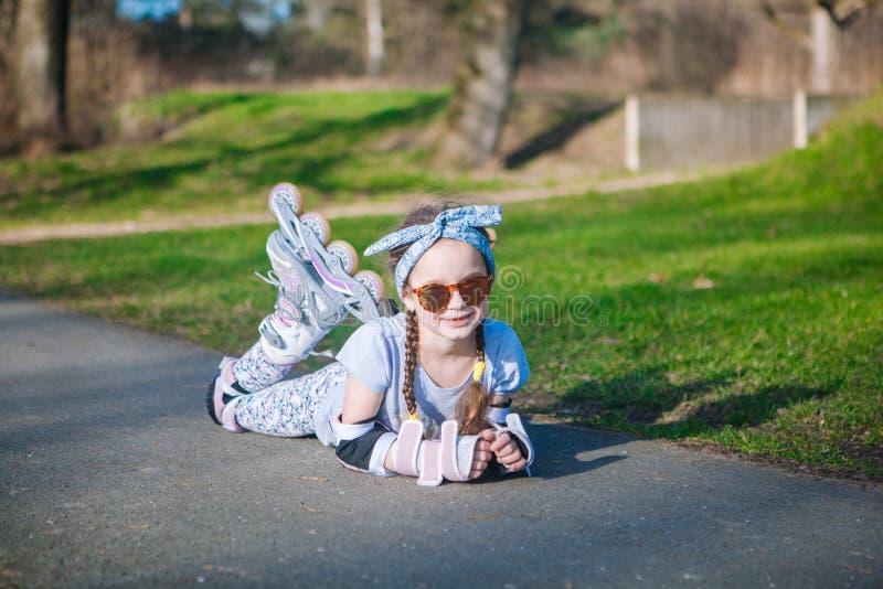 Encontro engraçado da menina encaracolado bonito em patins de rolo e vista da câmera foto de stock royalty free