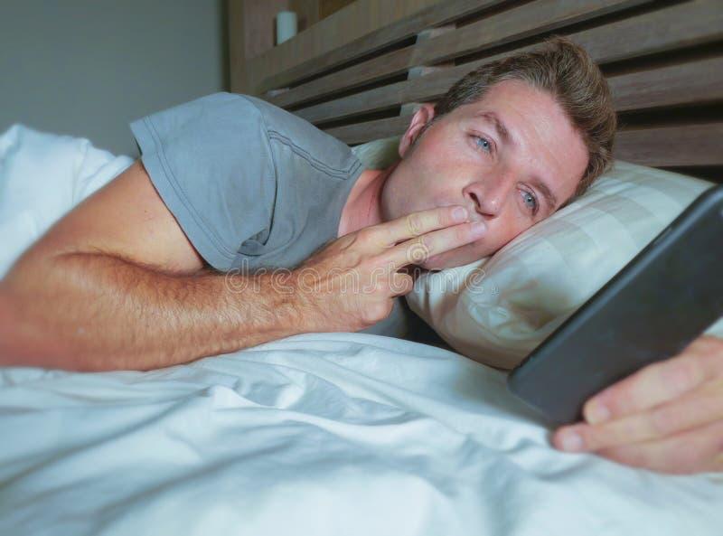 Encontro feliz de sorriso do homem atrativo novo na cama na noite usando os meios sociais app no telefone celular que tem a chama fotos de stock