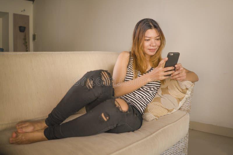 Encontro indonésio asiático atrativo e relaxado novo da mulher 30s confortável com utilização do sofá da sala de visitas do telef imagens de stock