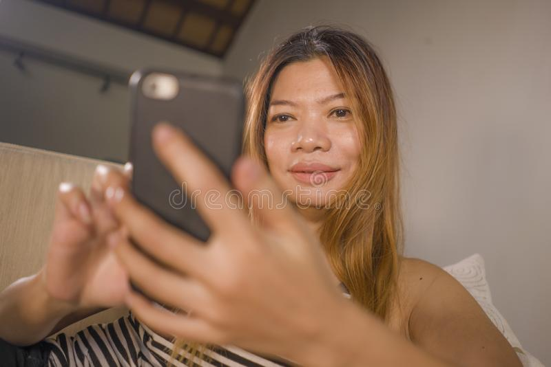 Encontro indonésio asiático atrativo e relaxado novo da mulher 30s confortável com utilização do sofá da sala de visitas do telef fotos de stock