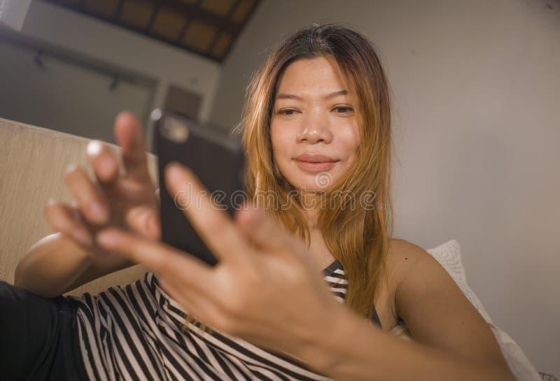 Encontro indonésio asiático atrativo e relaxado novo da mulher 30s confortável com utilização do sofá da sala de visitas do telef fotografia de stock royalty free