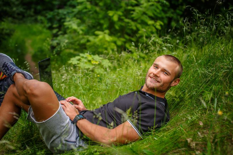 Encontro masculino caucasiano em uma grama e utilização do portátil fotografia de stock