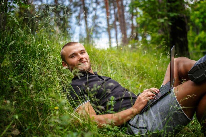 Encontro masculino caucasiano em uma grama e utilização do portátil foto de stock royalty free