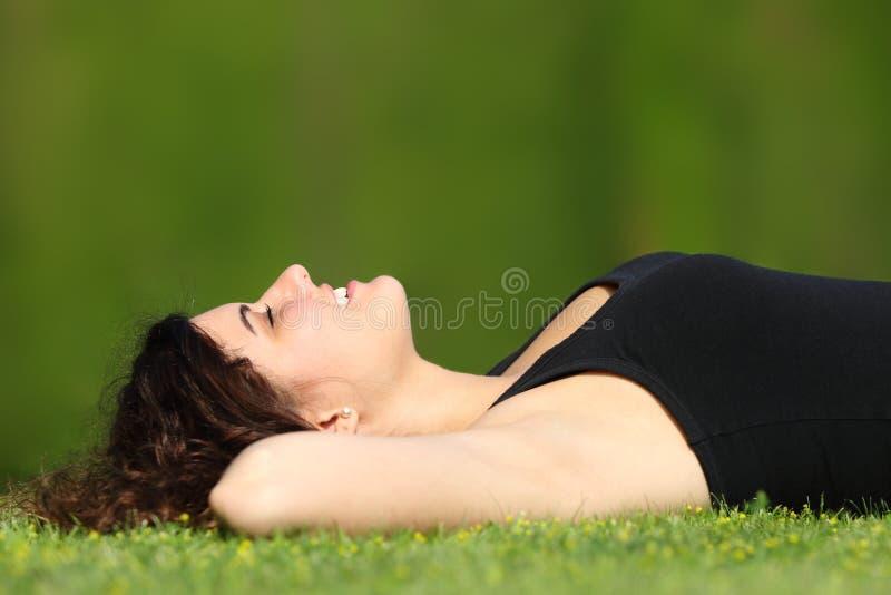 Encontro relaxado da mulher atrativa na grama em um parque imagem de stock