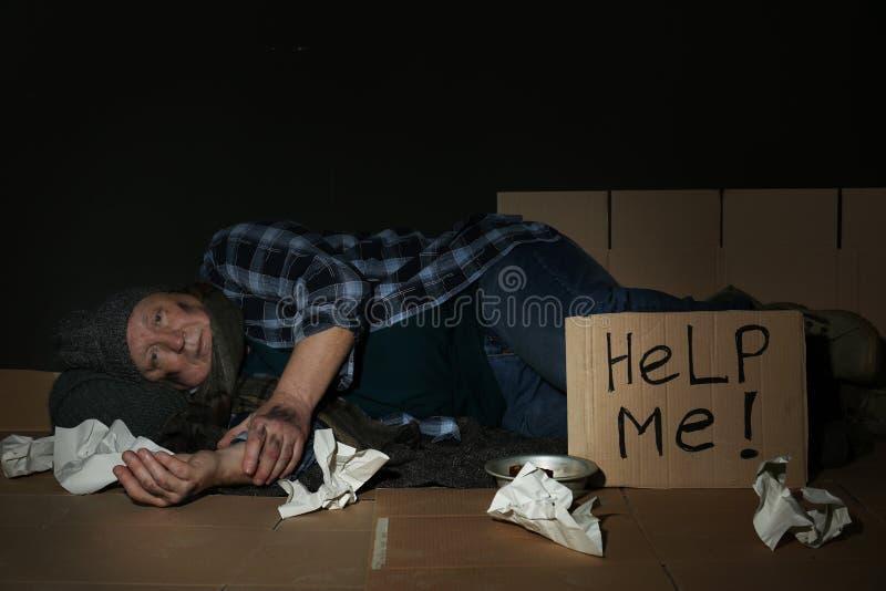 Encontro superior pobre perto do sinal do cartão PARA AJUDAR-ME no assoalho imagens de stock royalty free
