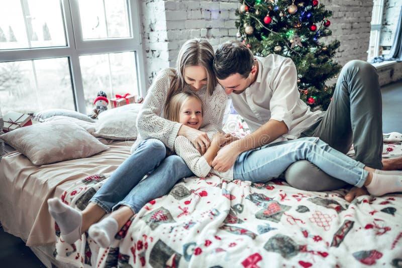 Encontro vestindo da família feliz na cama Mãe; pai e criança que têm o divertimento no tempo do Natal foto de stock