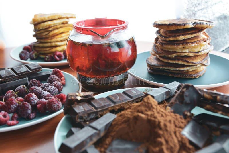 encore de la vie sur des assiettes bleues pancakes aux pois, chocolat râpé, barres chocolatées, thé brassé images stock