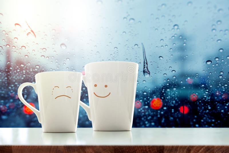 Encouragement concept. Friend of Coffee Mug with Sadness crying face cartoon and kindness happy face inside the room, Blurred city light and rain drop in city stock photos