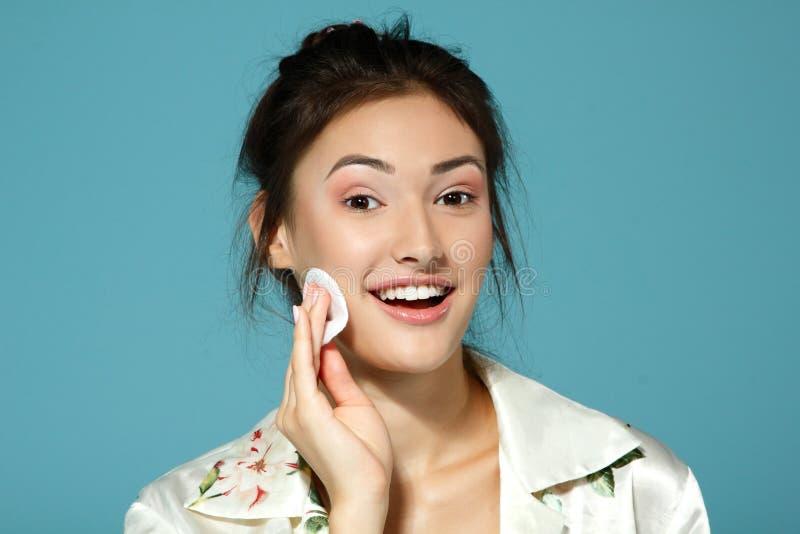 Encouragez la fille de l'adolescence attirante propre son visage avec le disque de coton matin image libre de droits