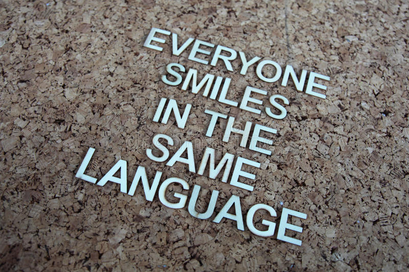 Encouraging words. That says Everyone smiles in the same language with a corkboard background in brown stock photography