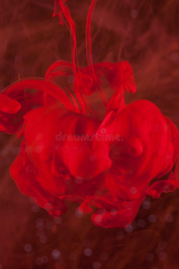 Encre rouge verticale dans l'eau sur le fond noir ressemblant à un troll images stock