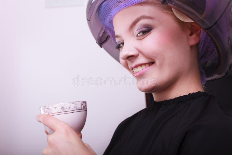 Encrespadores dos rolos do cabelo da mulher que bebem o salão de beleza do hairdryer do chá do café fotografia de stock